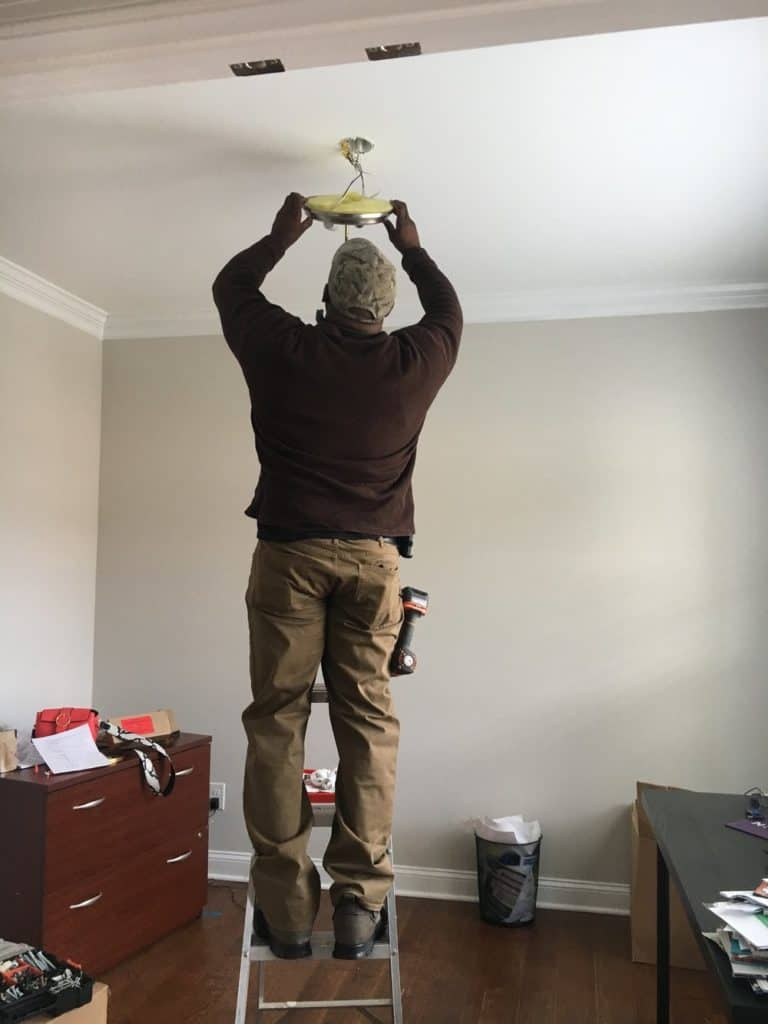 handyman installing office lighting